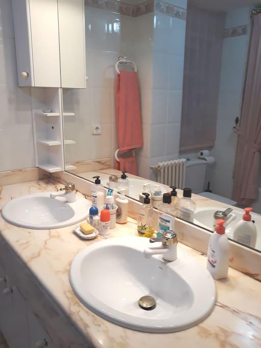 cuarto de baño con bañera y dos lavabos , al lado de la habitacion