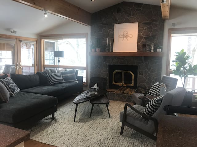Living room with wood burning fireplace and 60 inch television