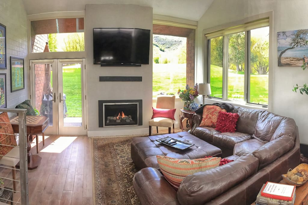 """The great room with new 65"""" flat screen tv, thermostat controlled fireplace and ultra comfy leather sectional couch."""