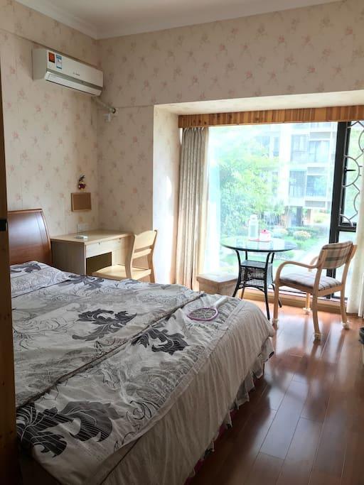 落地窗房间,大床,一台惬意的桌椅