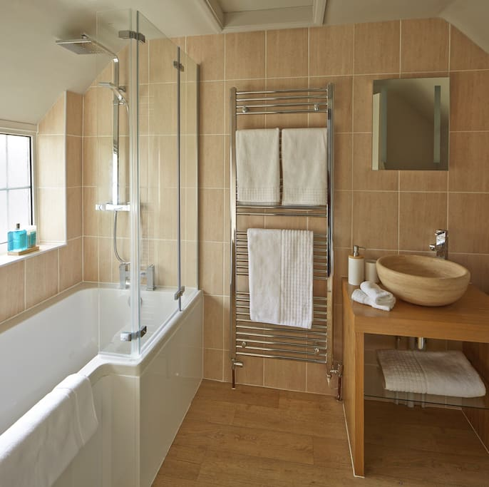 Beautifully appointed bathroom with thermostatic large head shower over bath.