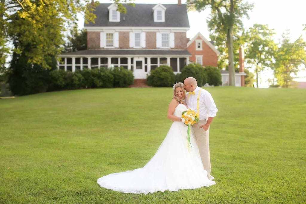 Newlyweds on the waterfront lawn with the Eagle Manor mansion in the background.