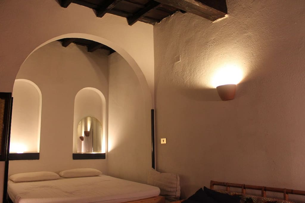 Large bed in an alcove, dark beams above.