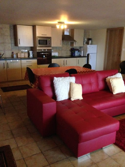 Main sitting room with fitted kitchen, dinning room table & chairs