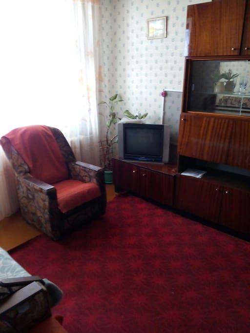 Спальная комната, здесь есть телевизор, кресло, стулья, шкаф
