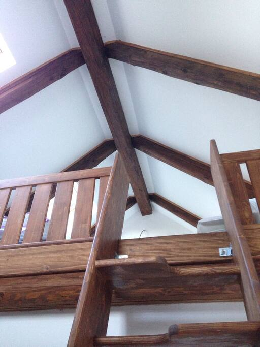 There are ladder-like stairs leading up to a sleeping loft, where there are two beds 90x200.