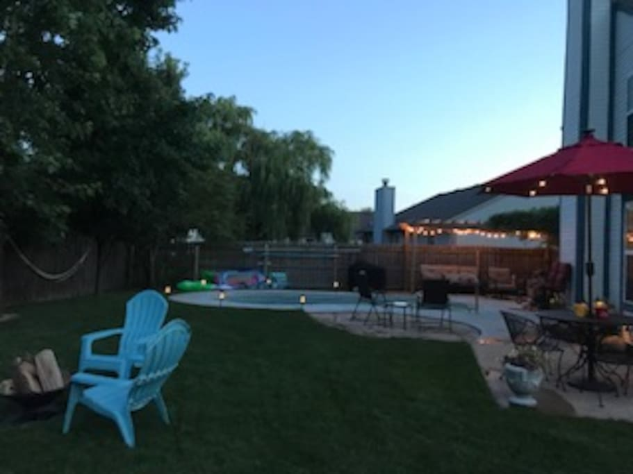 Partial view of fully fenced in back yard.  Pool, fire pit, dining and lounging area to enjoy outdoor weather