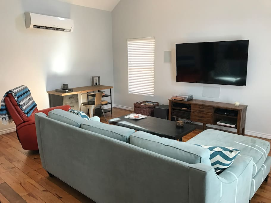 """Spacious living area with a 65"""" TV and surround sound (in wall and ceiling speakers)."""