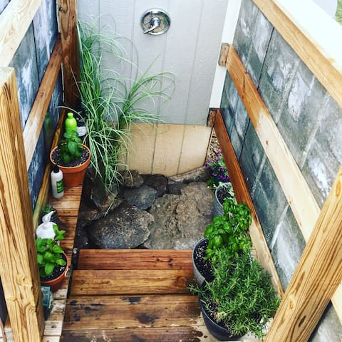 outdoor shower packed with fresh herbs & flowers