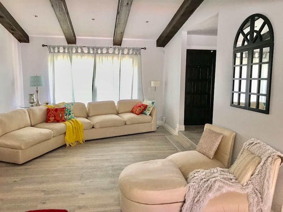 Formal living room with vaulted ceiling & wooden beams.