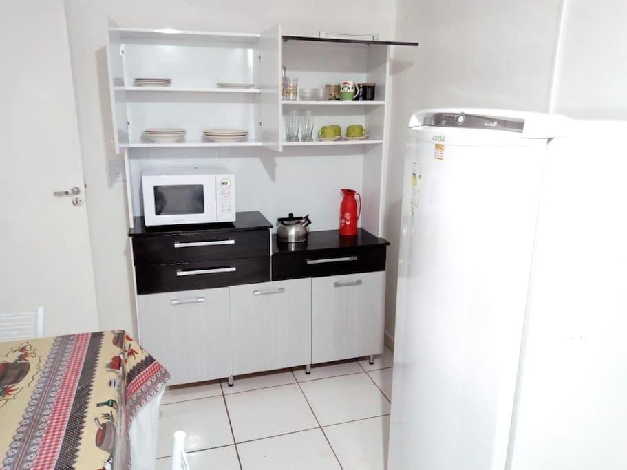 Geladeira, micro ondas e utensílios de cozinha.