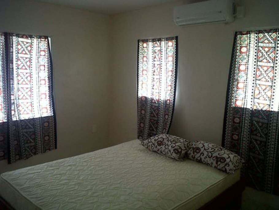 view of aircon bedroom with queen size bed.