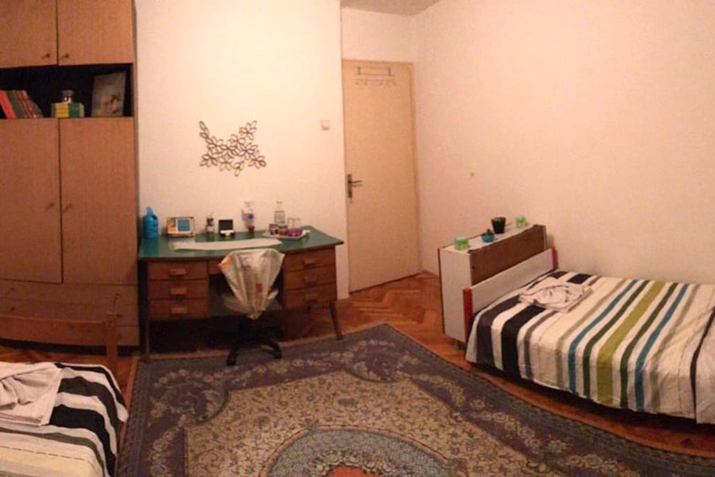 The whole room with two beds, a desk, and a wardrobe