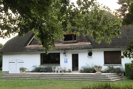 A beautiful thatched cottage in a large park