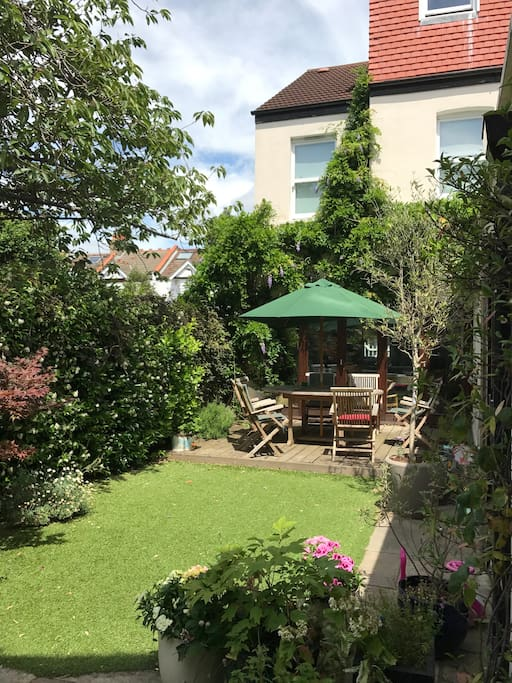 Small but pretty and extremely private back garden with artificial grass, (so it's perfect all year round!) we have wooden folding doors off the sitting room and kitchen, which is great in summer.