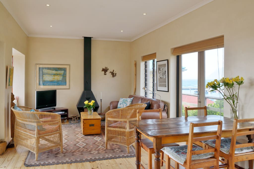 Open fireplace, TV, couches, dining area and views out to harbour