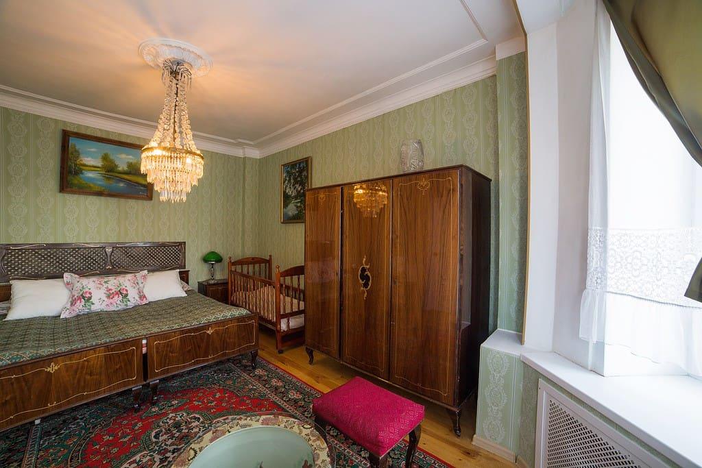 Просторная спальня с детской кроваткой. Основное украшение комнаты - панорамное эркерное окно и картины известного владимирского художника.