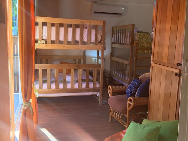 Orange Room. Down Stairs with views of the pool.  2 full size bunk beds, sleeps 4 people with own mattress.  attached bathroom, A/C and wifi.  Custom Cabinets made with exotic wood imported from Indonesia.