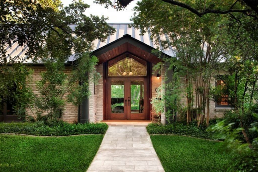 The private entry, behind tall hedges, is shaded by a substantial live oak.