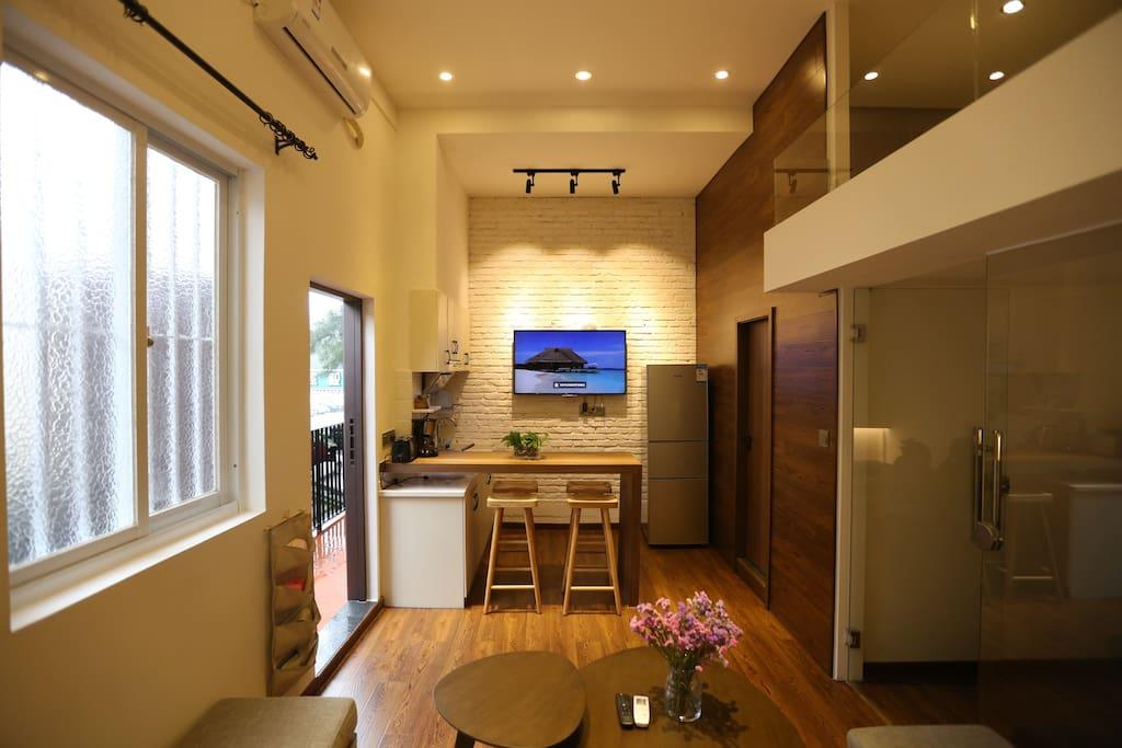 客厅一角,吧台、55寸高清液晶网络电视、三开门冰箱。