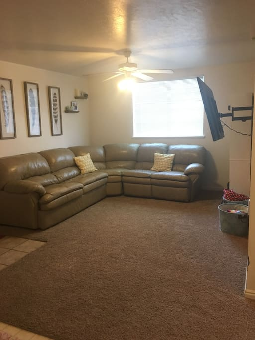 living room with large sectional including hide-a-bed and two recliners, 55 inch TV with access to Xbox One (with netflix and hulu), directTV, and a DVD player