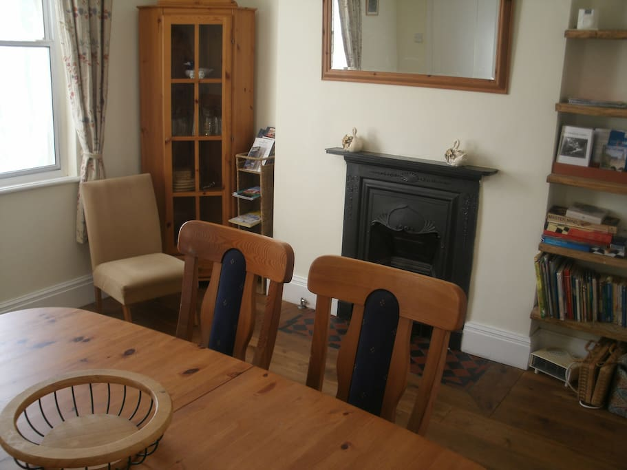 Dining room showing glasses cabinet, toys, books and dining table which seats 6 or more.