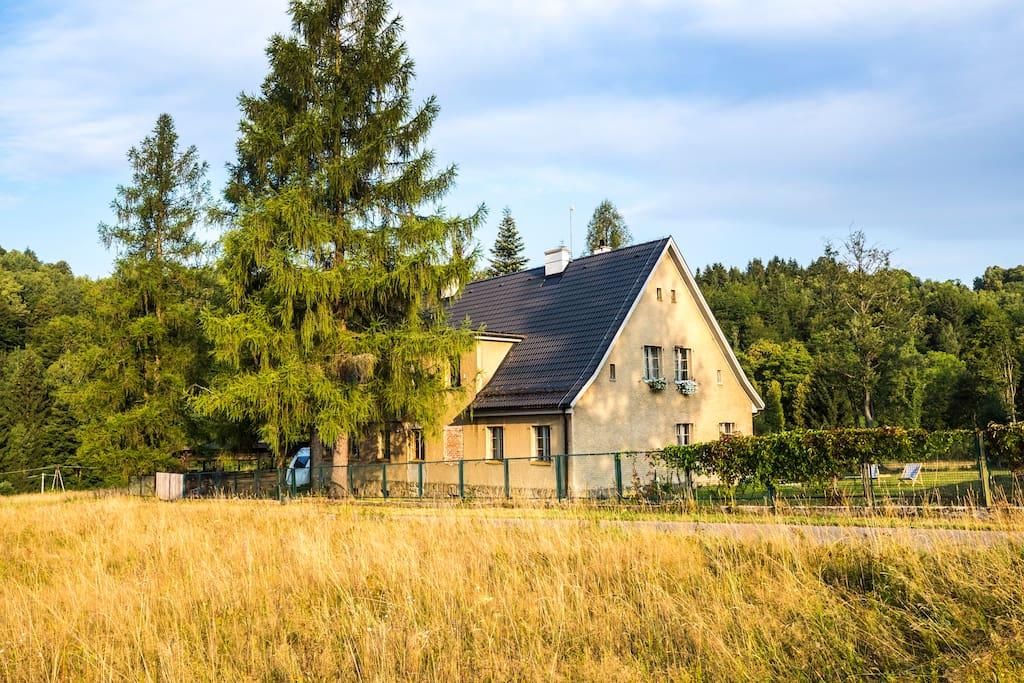 Dom usytuowany jest na odludziu, w rozległej górskiej dolinie pośród łąk.
