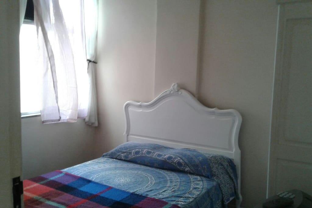Quarto com cama de casal, armário de duas portas e ar condicionado.