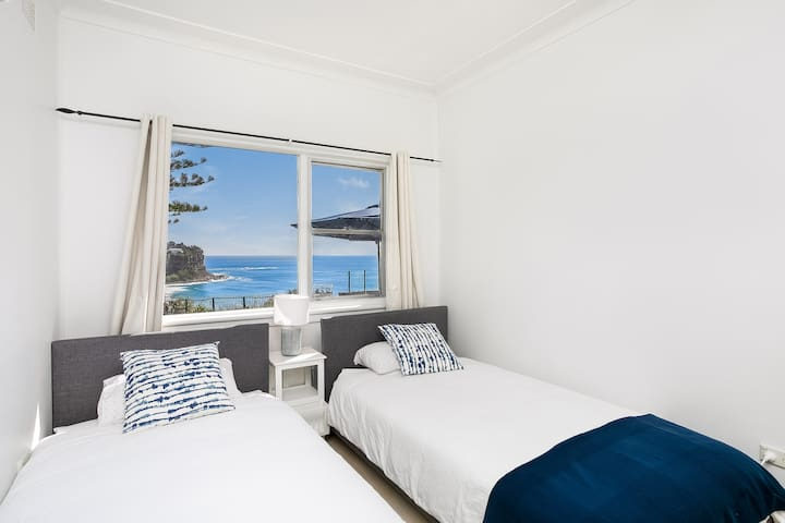 Bedroom with two king single beds and a view