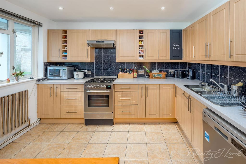 Spacious kitchen with dinner table and stools. All amenities: oven, microwave, dishwasher, fridge, toaster etc