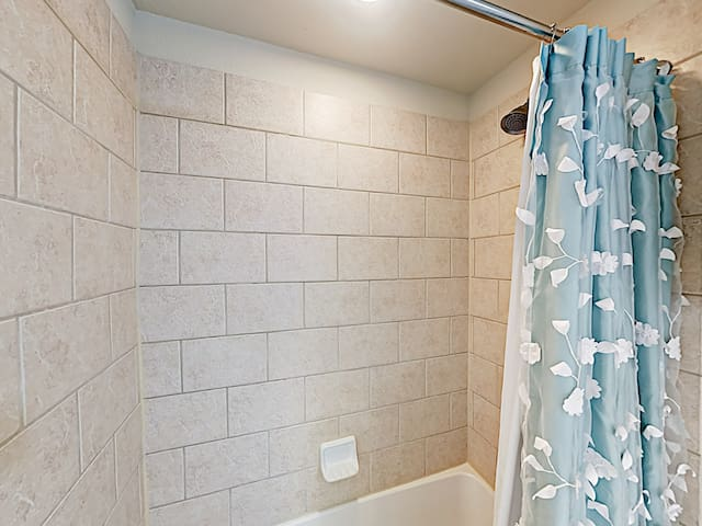 The guest bathroom is configured with a tub/shower combination.