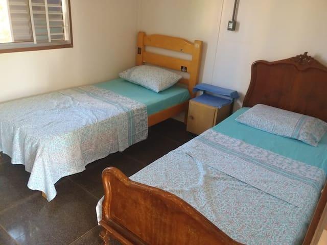 Quarto 2.  2 camas de solteiro, criado mudo, cômoda com gavetas e TV com Internet.