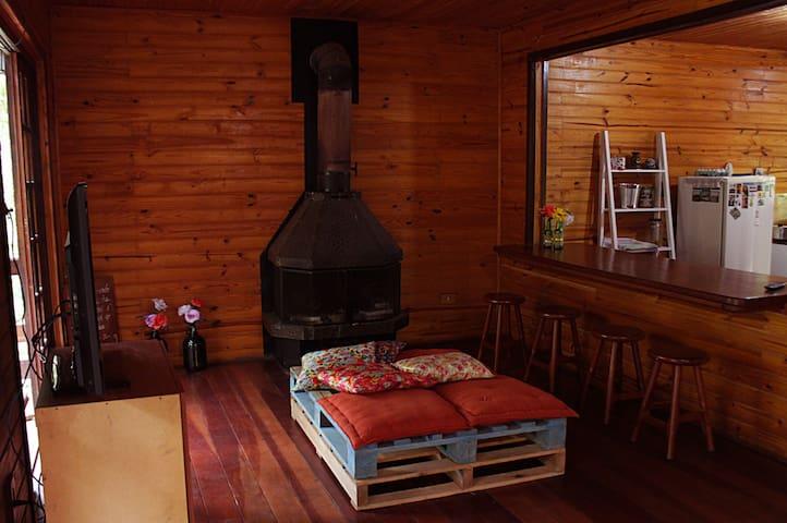 Sala de estar com tv, lareira e cozinha americana.