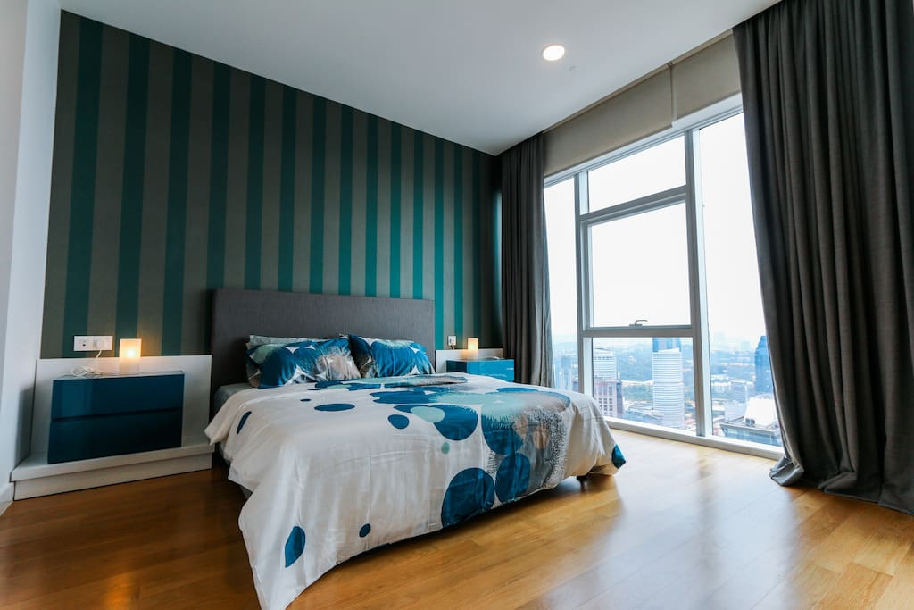 Master bedroom with a King size bed soothing yellow light and aircond with a breath taking city view