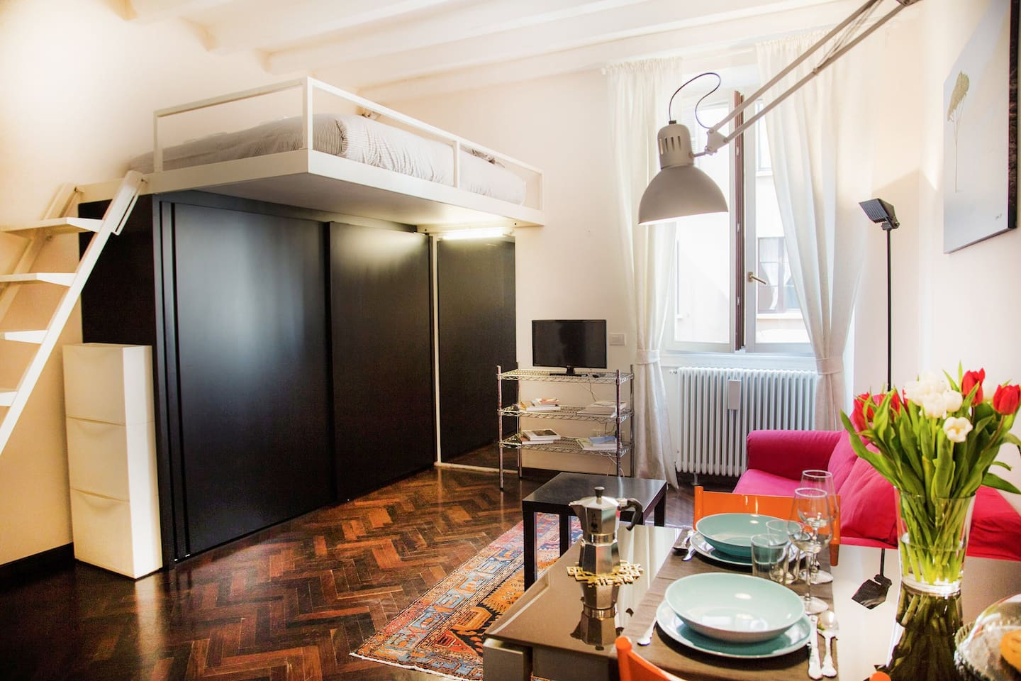 A wide studio apartment, full of light and colour