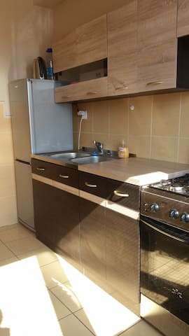 Spacious kitchen with fridge, stove, kettle, pots and pants and a sitting area.