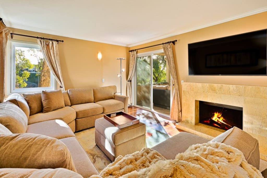 Large tv room with plenty of space for the whole family to sit by the fireplace.