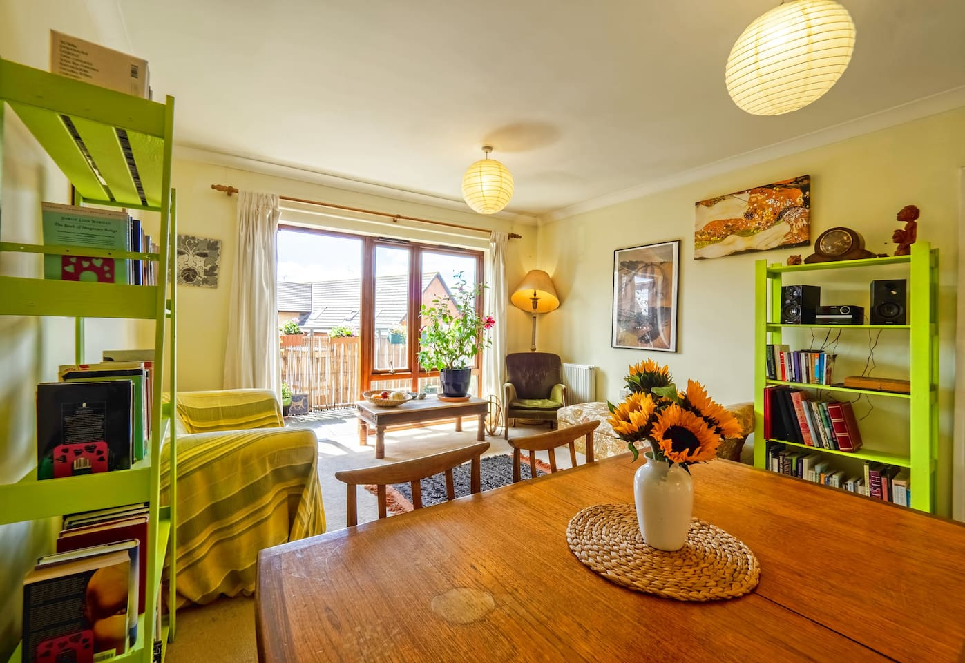 bright lounge/dining room with access to balcony. Feel free to take a chair outside on summer's evening!