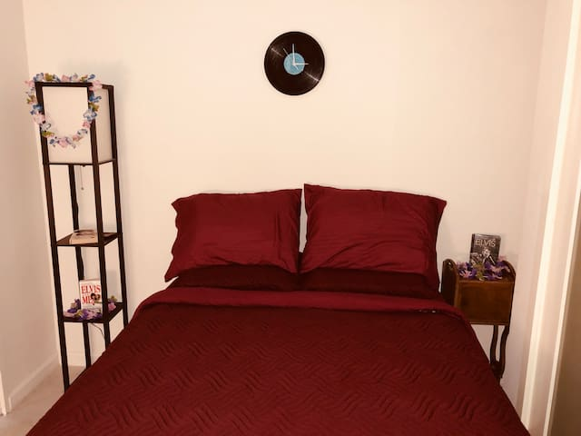 Full size bed, with a real spring mattress, under an Elvis Vinyl clock