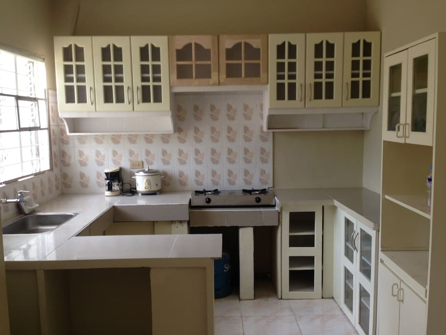 Furnished kitchen with refrigerator, two burner gas stove , cabinets and tiled counter top with breakfast nook