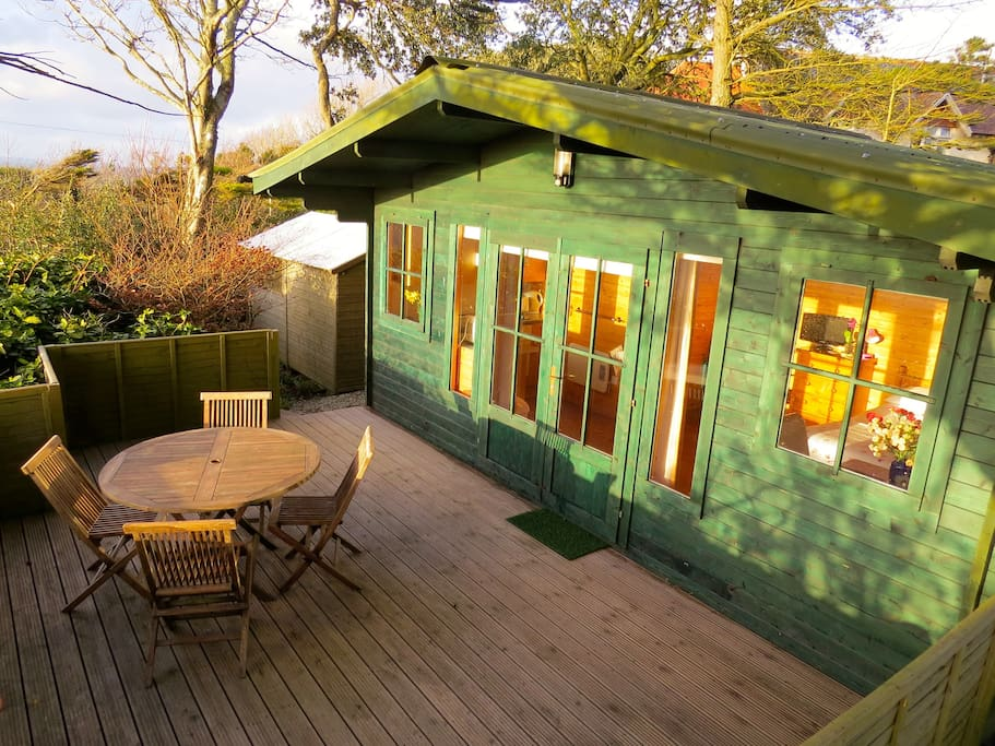 The pine cabin is organically painted, with private decking and stunning views of the sea