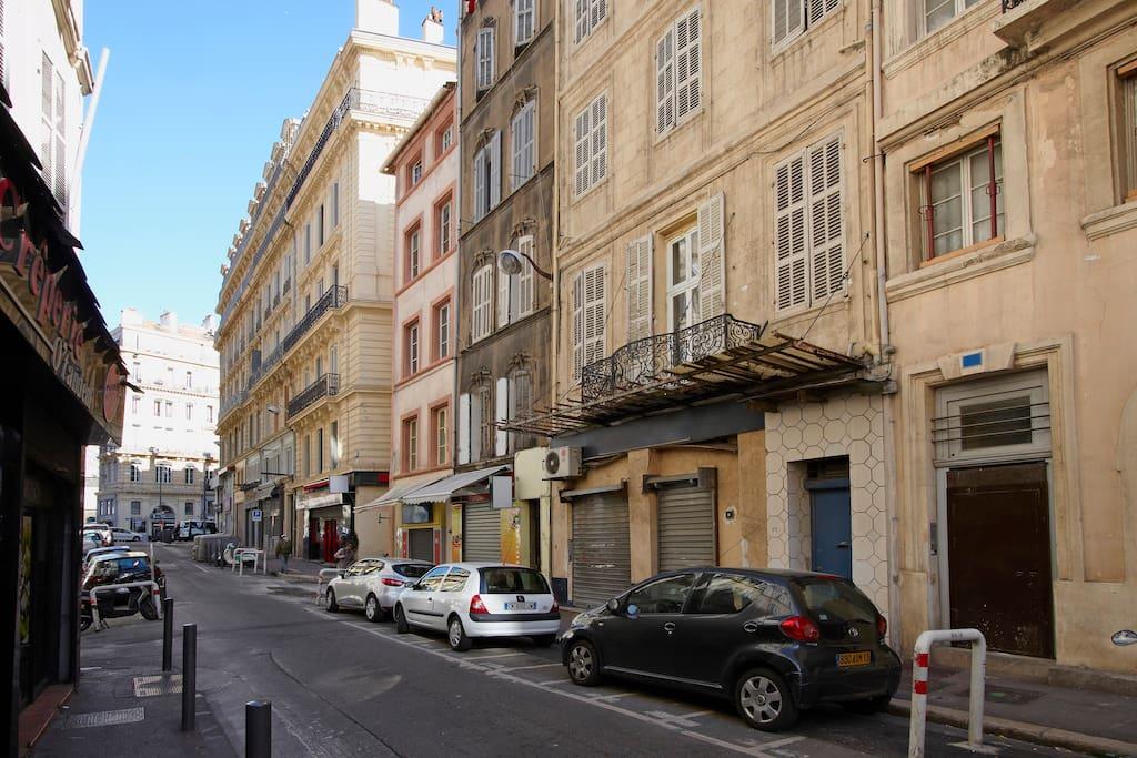 C'est le petit immeuble gris avec les moulures à côté du rose avec au bout la fameuse rue commerçante de la République.
