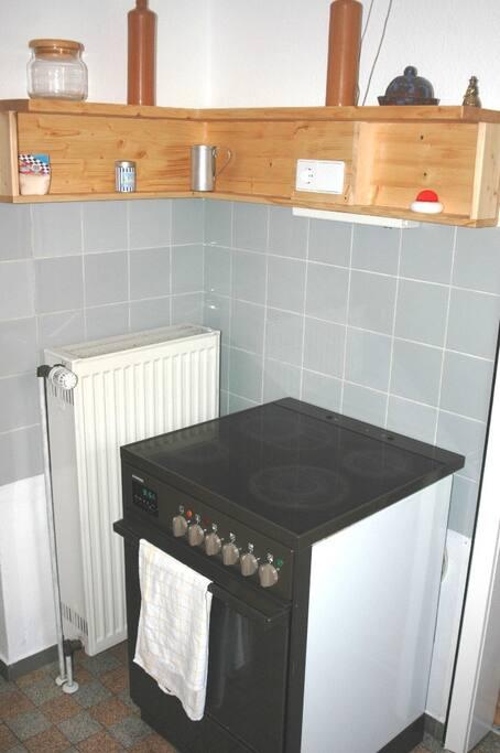In der Küche finden Sie eine Herd mit vier Kochplatten und einem Umluft-Backofen, außerdem einen Küchenblock mit Doppel-Waschbecken. Im Nebenraum befindet sich ein Kühlschrank (mit Gefriereinheit) sowie Regale für Ihre Vorräte.