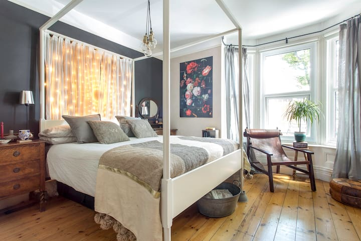 The master bedroom features a comfortable four poster bed.