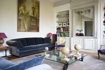 Salon du Château, bibliothèque, TV, piano.
