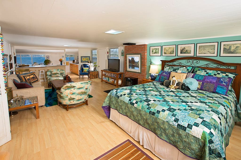 Interior showing hand made quilt on comfortable king bed, main living area with view of Morro Bay beyond.