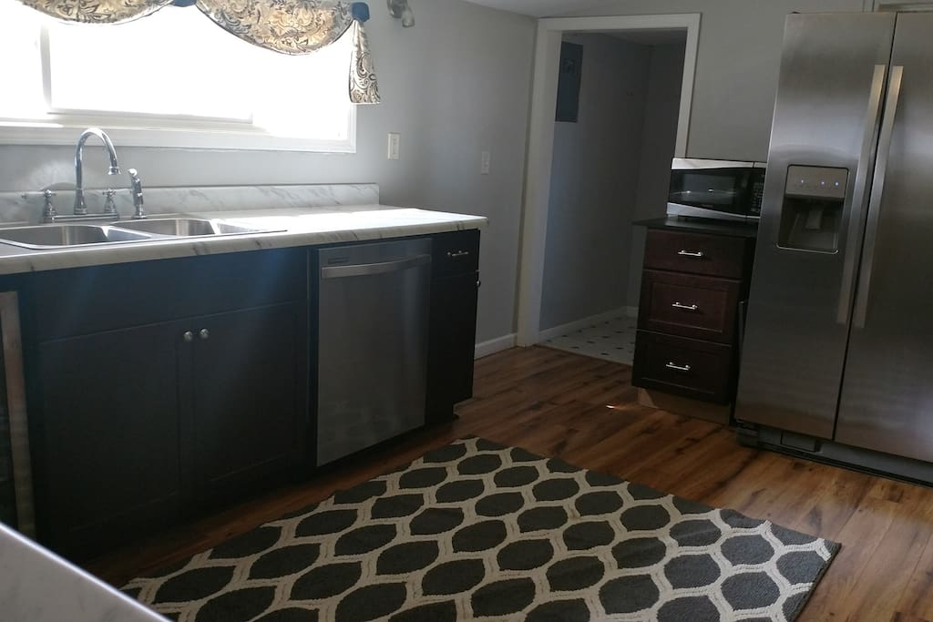 Kitchen Featuring Refrigerator, Microwave, Stove and Beverage Cooler