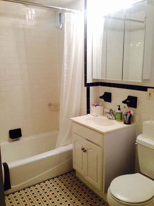 Cute fully tiled modern bathroom towels and products provided.