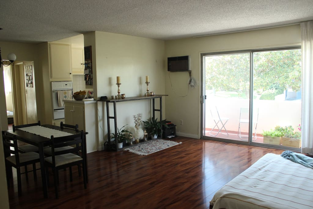 Spacious living room with balcony. Gets lots of sun in the afternoons.
