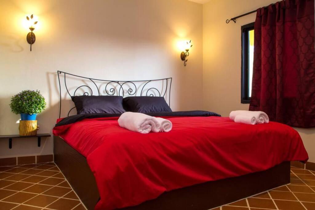 เตียงใหญ่ ผ้านวมหลากสีสัน ม่านทึบแสง กระเบื้องดินเผาคลาสสิก